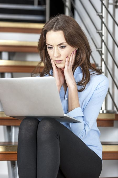 Young woman using a laptop computer looking concerned and worried