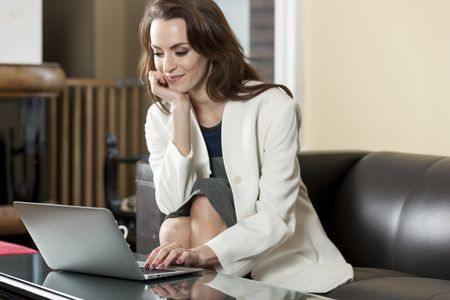 Professional business woman using her laptop computer while relaxing