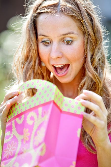 Suprised woman opening a gift outdoors