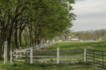 Haven for retired horses: Shaded paddock, enclosed by long weathered fence with iron gate, at a public equestrian center in spring, northern Illinois