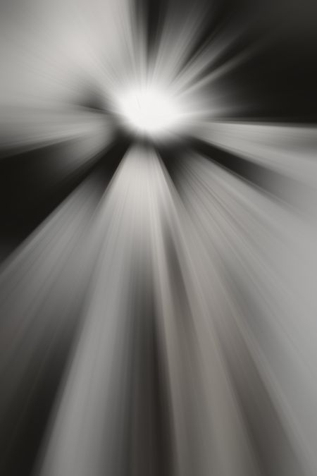 Black and white radial blur of bright object emitting rays in every direction, for themes of origin, radiance, interstellar travel