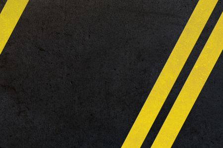 asphalt background with double yellow lines on an angle