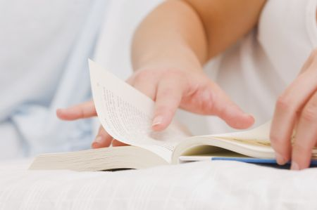 Close up of a girl reading a book on her bed.