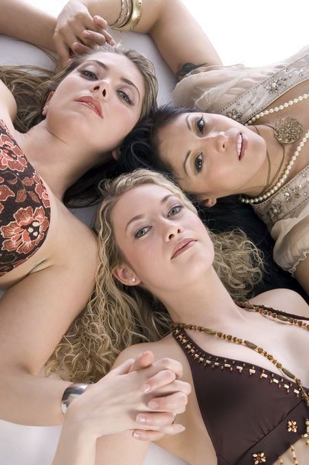 Three glamorous young women friends, heads together and looking up