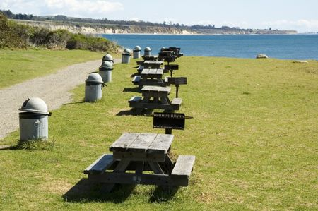 Row of picnic tables, grills, and garbage cans in public park along coastline