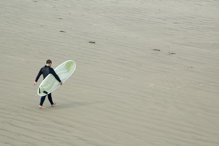 Adult male surfer carries stylish surfboard across sandy beach toward shallow waves