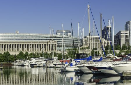 Urban magnetism: Row of yachts docked in Burnham Harbor by Soldier Field, home of the Chicago Bears professional football team, along the lakefront on a sunny spring morning in Chicago