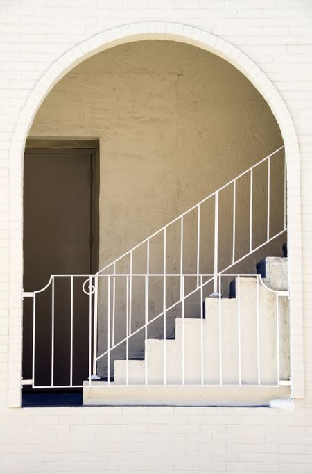 Arch and recessed door, guardrails, and stairway at side of white brick building in southwestern United States