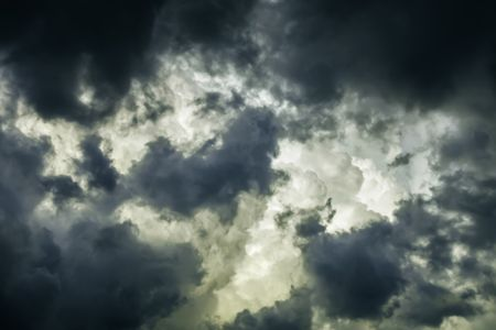 Storm clouds in summer: Ragged wind-driven dark clouds move in quickly to obscure large white billows before sunset, for meteorological themes of instability and rapid change
