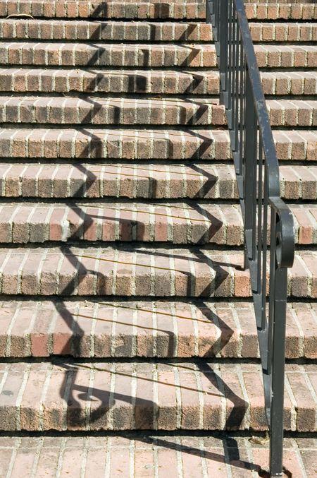 Zigzag shadows of black handrail on red brick stairway on college campus