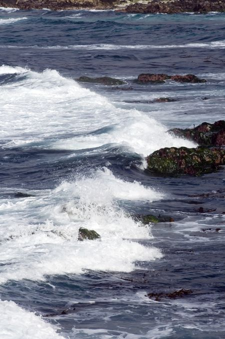 Ocean waves breaking white toward dark rocks near shore