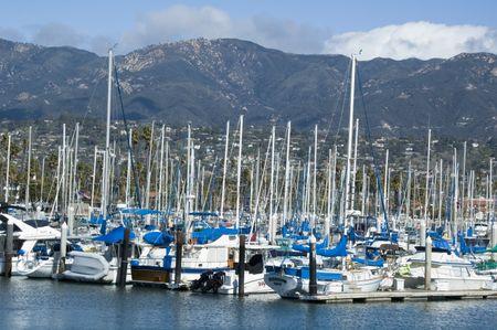 Many yachts in marina, city and mountains beyond, Santa Barbara, California