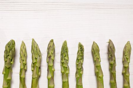 fresh raw asparagus on a light wooden kitchen work surface