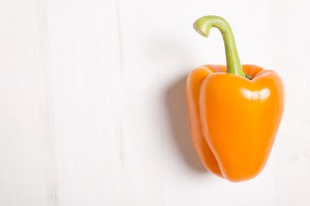 Fresh orange bell pepper on a light wooden kitchen surface