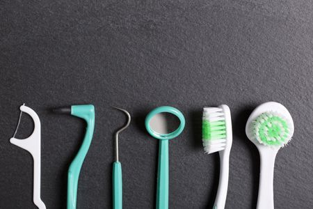 Selection of dentist brushes and tools on a black slate surface