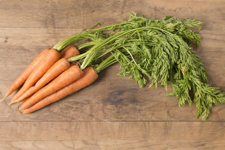 Selection of fresh raw carrots on a wooden kitchen work surface