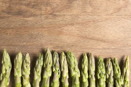 Fresh raw asparagus on a wooden kitchen work surface