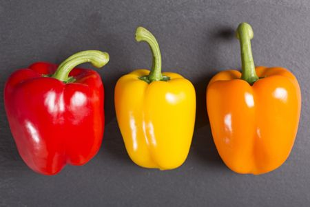 Fresh selection of ripe red yellow and orange peppers on black slate