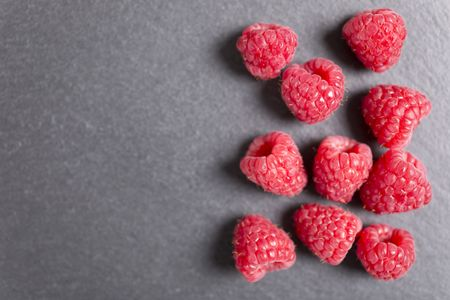 Fresh ripe summer raspberries on black slate