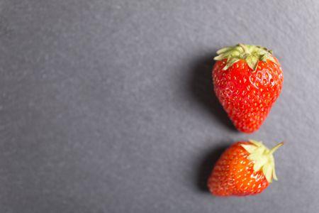Fresh ripe strawberries on black slate