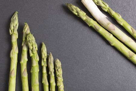Selection of fresh Asparagus on black slate with copy space