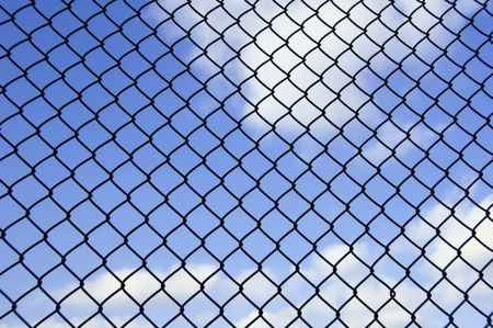 Barrier to dreams: Mesh fence with partly cloudy sky beyond