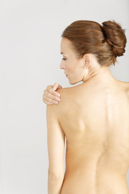 Young woman facing away massaging her shoulder from an ache or pain