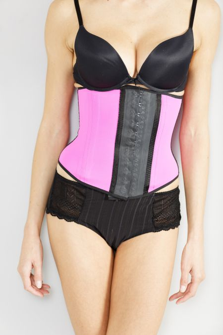 Young woman wearing a waist training corset in black underwear which is the new craze for looking slim