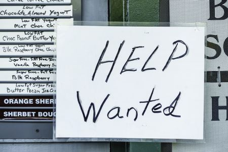 """Laminated handwritten """"Help Wanted"""" sign in window of ice cream and yogurt shop in tourist town"""