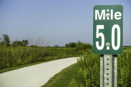 Marker at mile 5 by gravel path across prairie preserve for joggers, bicyclists, and hikers in west suburban Chicago, USA, in summer