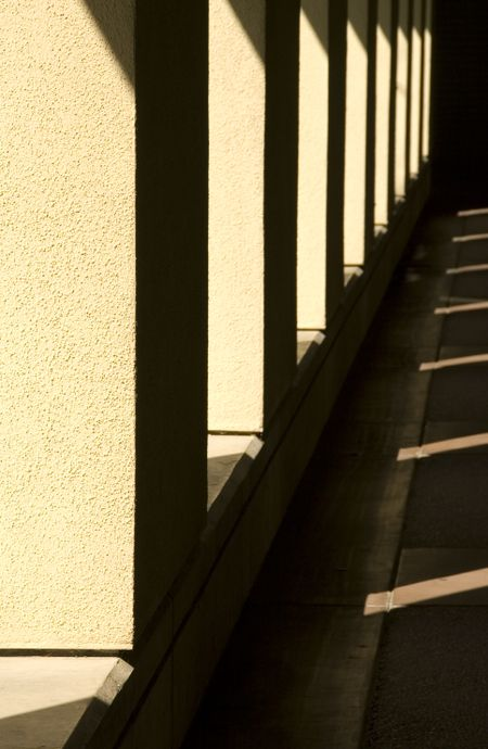 Passageway with sunlight and shadow outside building on college campus in southern California (focus on nearest stucco column)