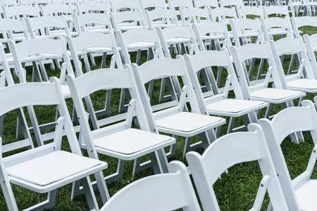 Symmetry of love: Rows of white folding chairs on lawn before a wedding ceremony in summer