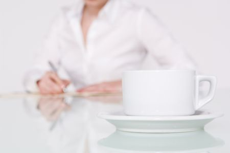 Close up of a coffee cup with businesswoman writing in background.