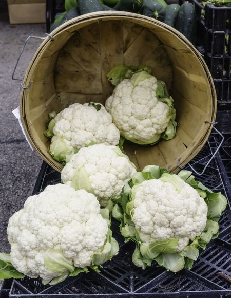 Five white cauliflowers, two still in the basket, on display cornucopia-style at a farmer's market (foreground focus)