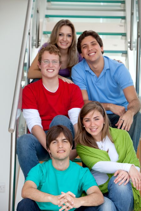 Casual group of friends sitting on the stairs smiling