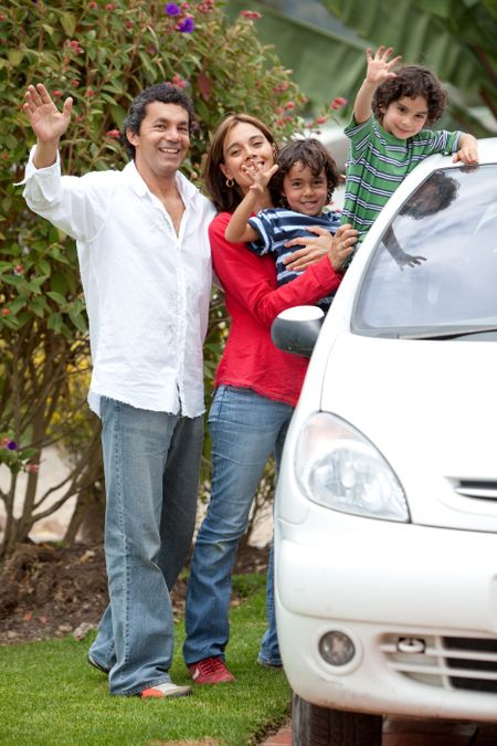 Lovely family waving and smiling from the car