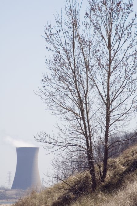 Global warming in brief - tree on hillside in foreground, power plant in background