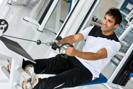 Strong gym man exercising on a machine