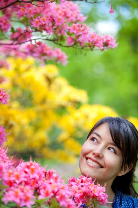 casual woman smiling outdoors with some flowers