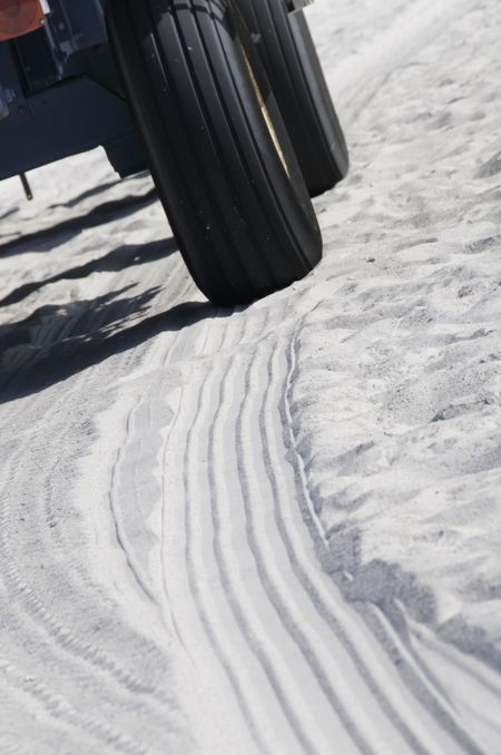 Tire tracks of beach buggy in white sand
