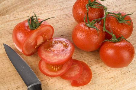 Fresh red tomatoes on a chopping board