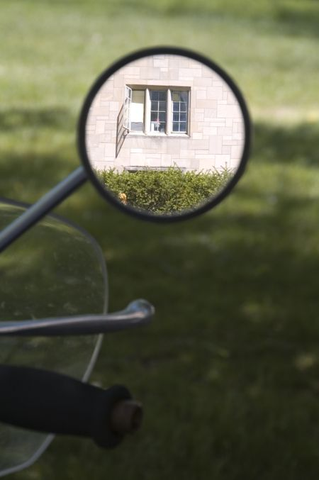 Rearview mirror on motorcycle in shade reflects window of university building in sunlight