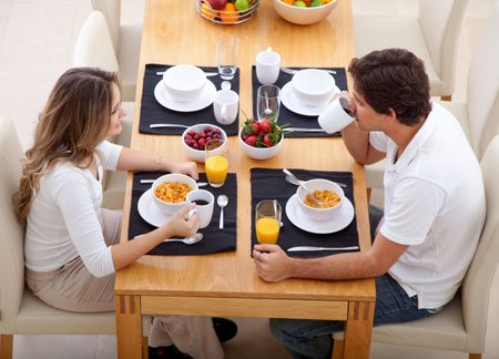 Beautiful couple eating their breakfast at home