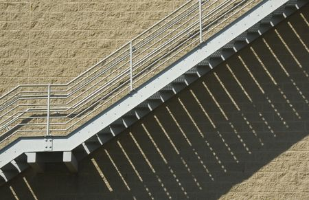 Exterior steel staircase with shadow pattern on brick wall of college athletic facility