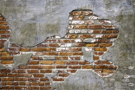 Vintage architectural grunge: Old brick exposed beneath thin concrete fallen off face of exterior wall