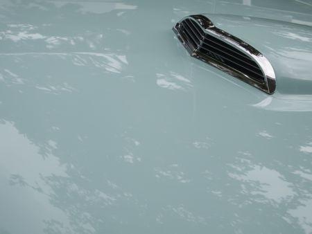 Air intake on reflective light green hood of classic car