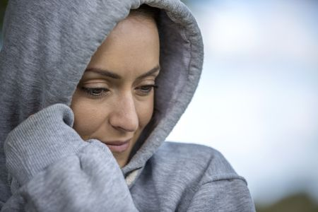 Young woman on a cold morning in a hooded top before going out for a run