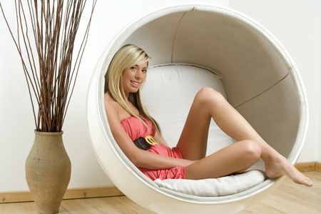 Woman relaxing in an egg chair
