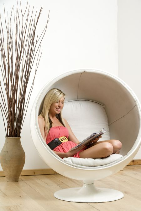 Woman relaxing and reading in an egg chair