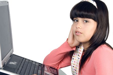 Pretty brunette schoolgirl in pink looks at you, notebook computer in front of her, isolated on white